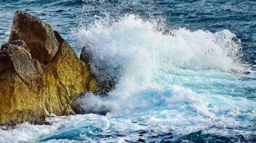 Ocean waves crashing into rock